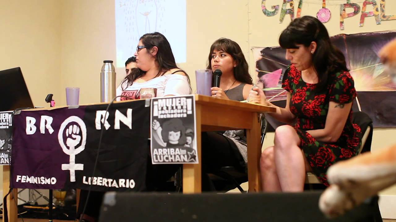 Three women sit behind a table giving a panel presentation.