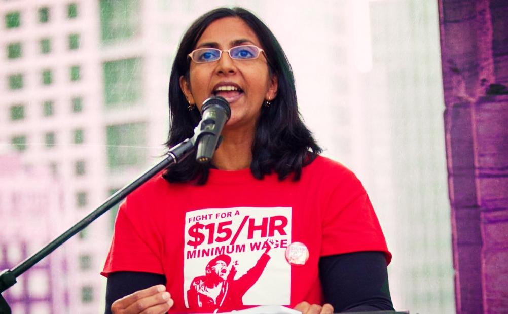 Photo of Kashama Sawant speaking from a podium, an urban tower is the background.