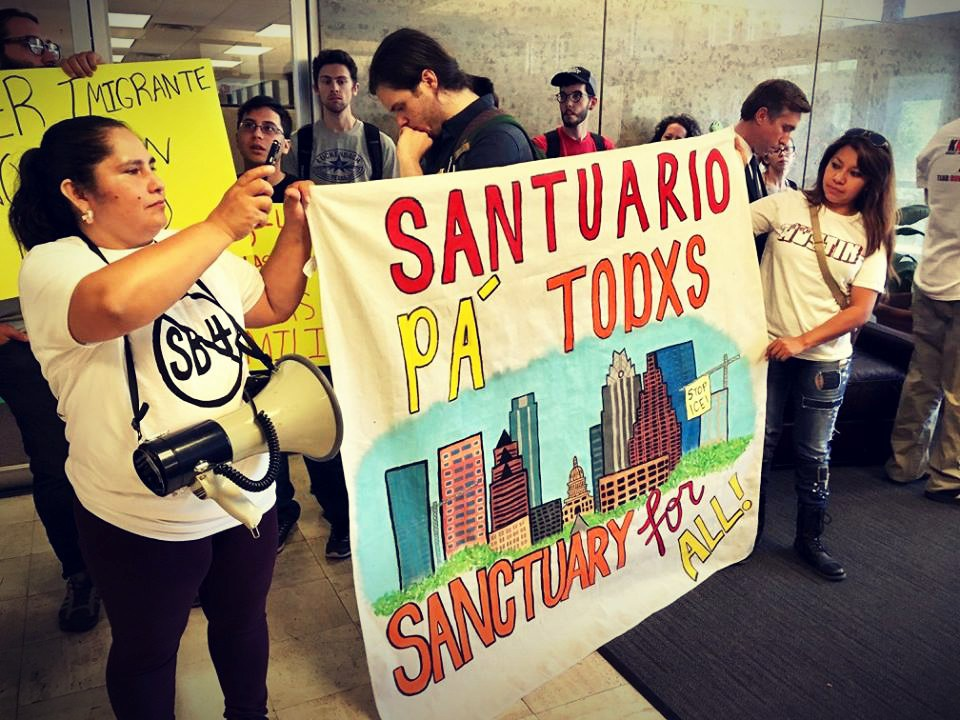 "Protesters holding banner ""Sanctuary for all"""