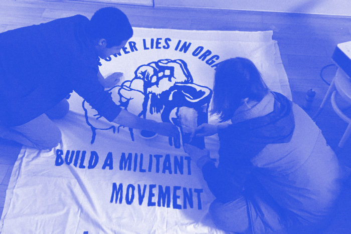 "Photo of two individuals making banner with slogan ""Our power lies in organization, build a militant tenant movement"""