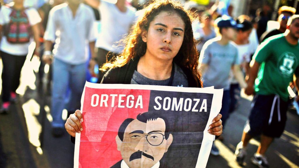 Image shows a woman carrying a sign during a protest than compares current president Ortega to Nicaraguan dictator Somoza