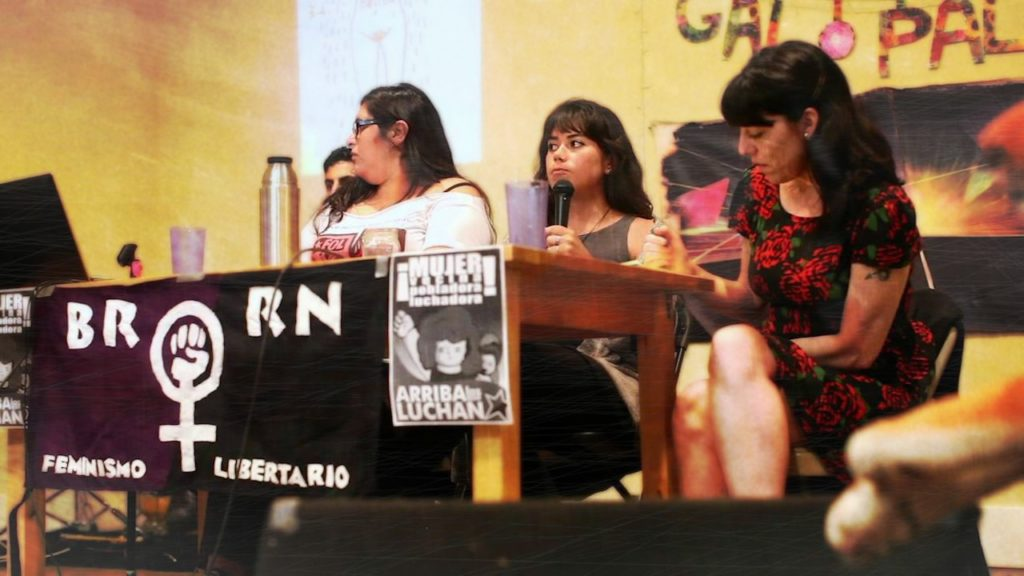 Three women sit behind a table giving a presentation.