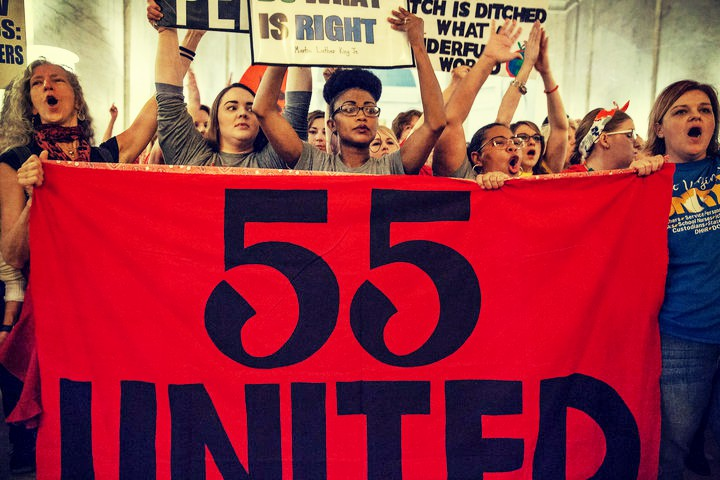 "West Virginia teachers behind banner with ""55 United"""