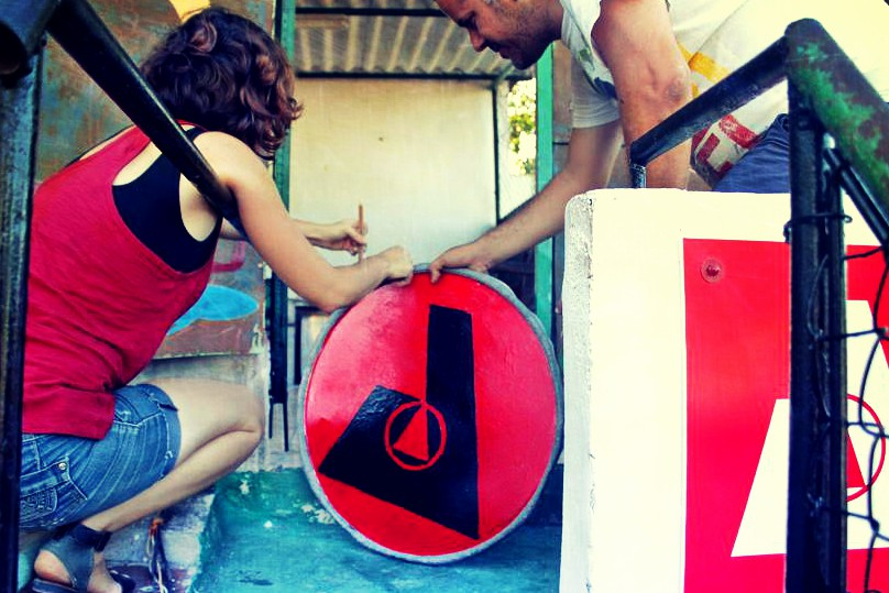 Two cuban anarchists prepare a sign with logo of Abra social center to be hung