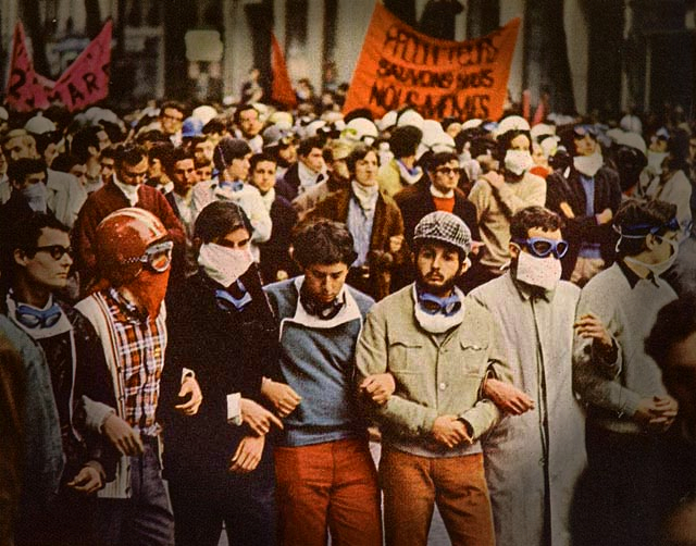 Young demonstrators, arms linked and banners in the background, march during the France 1968 rebellion.