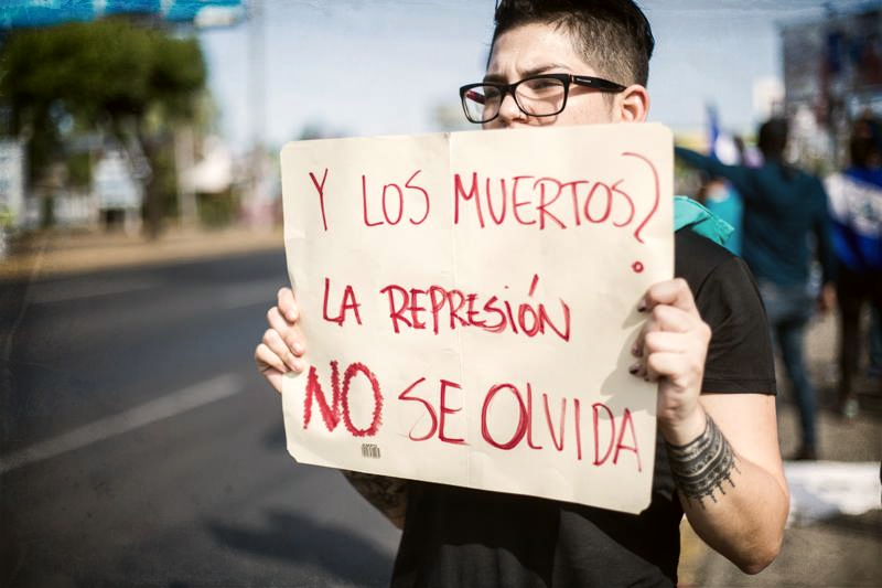 "Young person holding sign ""Y los muertos? La represion no se olvida / And the dead? We won't forget the [police] repression"""