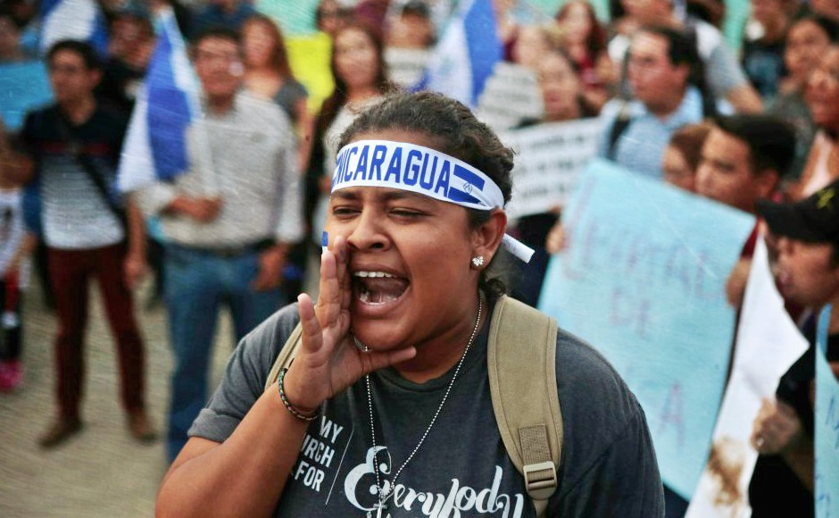"Woman leading chant with head band with blue text ""Nicaragua"""