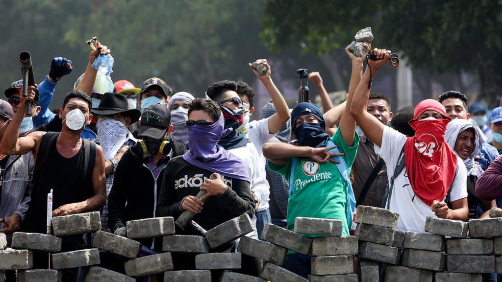 Young men behind a barricade of stacked paving stones, with raised fists and carrying homemade launchers for fireworks.