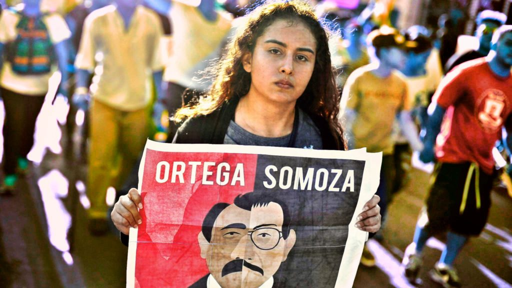 Woman carrying sign comparing former Nicaraguan dictator Somoza with current President Daniel Ortega