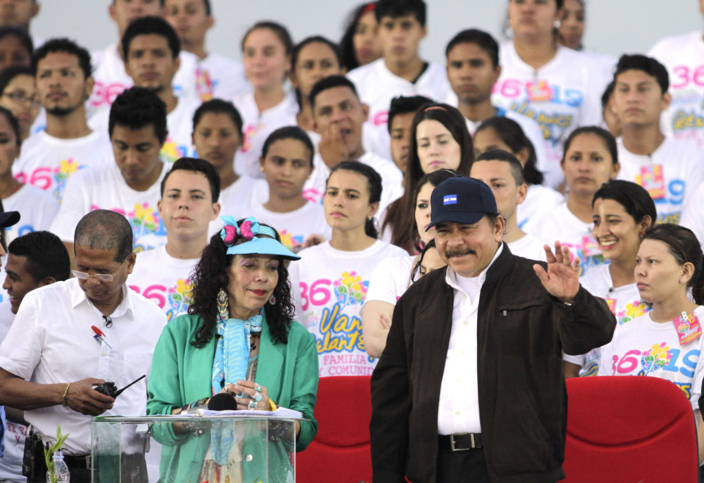 President Ortega flanked by Sandinista Youth with their distinctive shirts