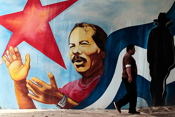Wall mural of Ortega with national flag and red star.