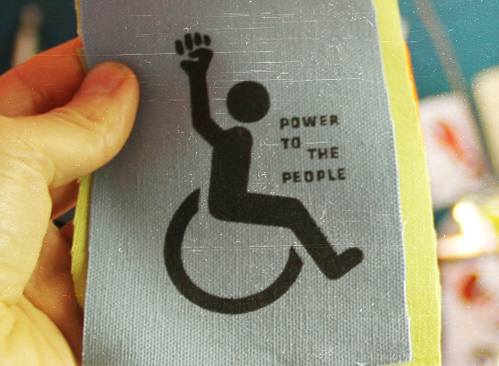 "Photo of a screen printed patch with outline of wheel chair symbol with raised fist and words ""Power to the people."""