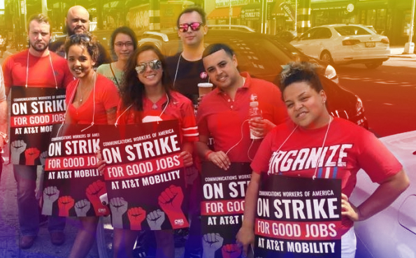 Group of striking AT&T workers posing together with red shirts and strike signs.