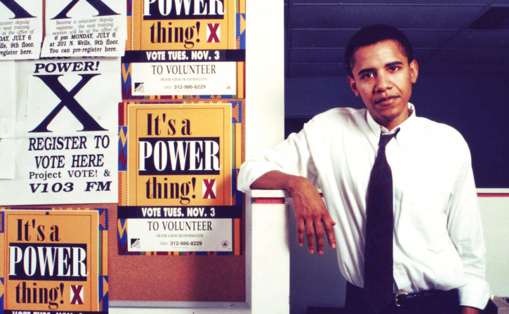 "Photo of Barack Obama in his early years as a community organizer in Chicago. He is pictured next to pro-voting signs such as ""It's a POWER thing! X"""