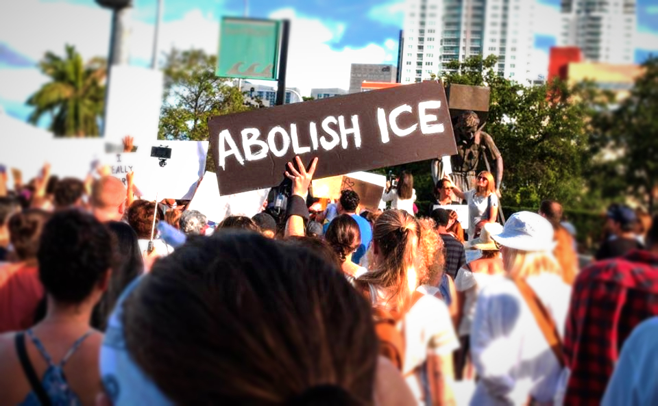 "Crowd marching in protest of detention of migrants and children in Miami. Handmade sign in center says ""Abolish ICE"""