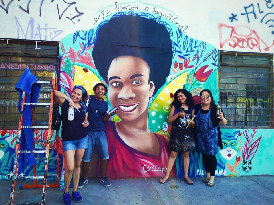 Four woman posed for picture in front of wall mural with painting tools in hand.