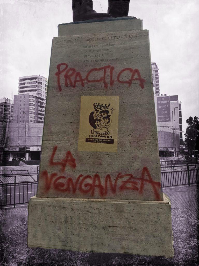Statue in park with red graffiti and a wheat pasted poster.