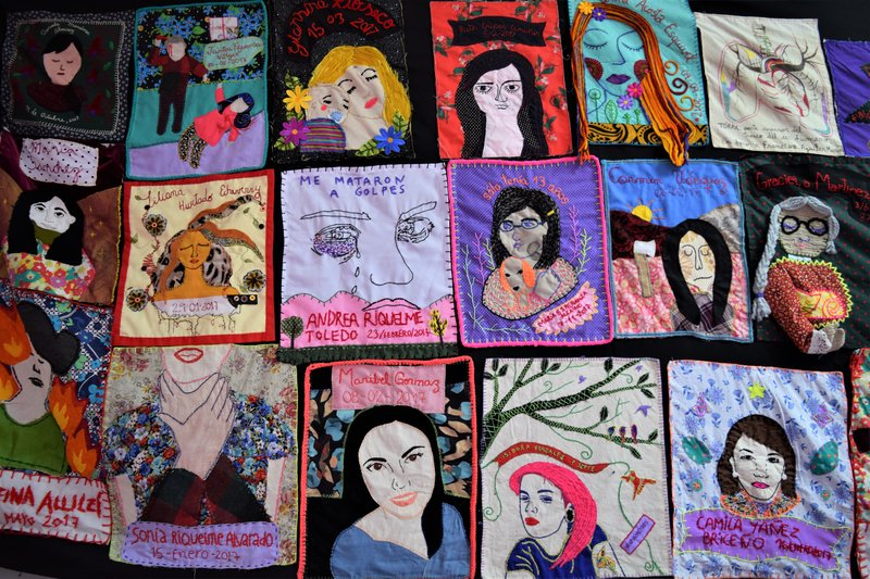 Quilt composed of squares portraying woman lost to femicide along with names.