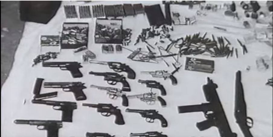 Black and white photograph of cache of guns authorities seized from an armed revolutionary group in Uruguay.