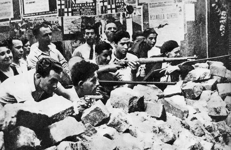 Photo of men lined up behind barricade of stones, guns at the ready.