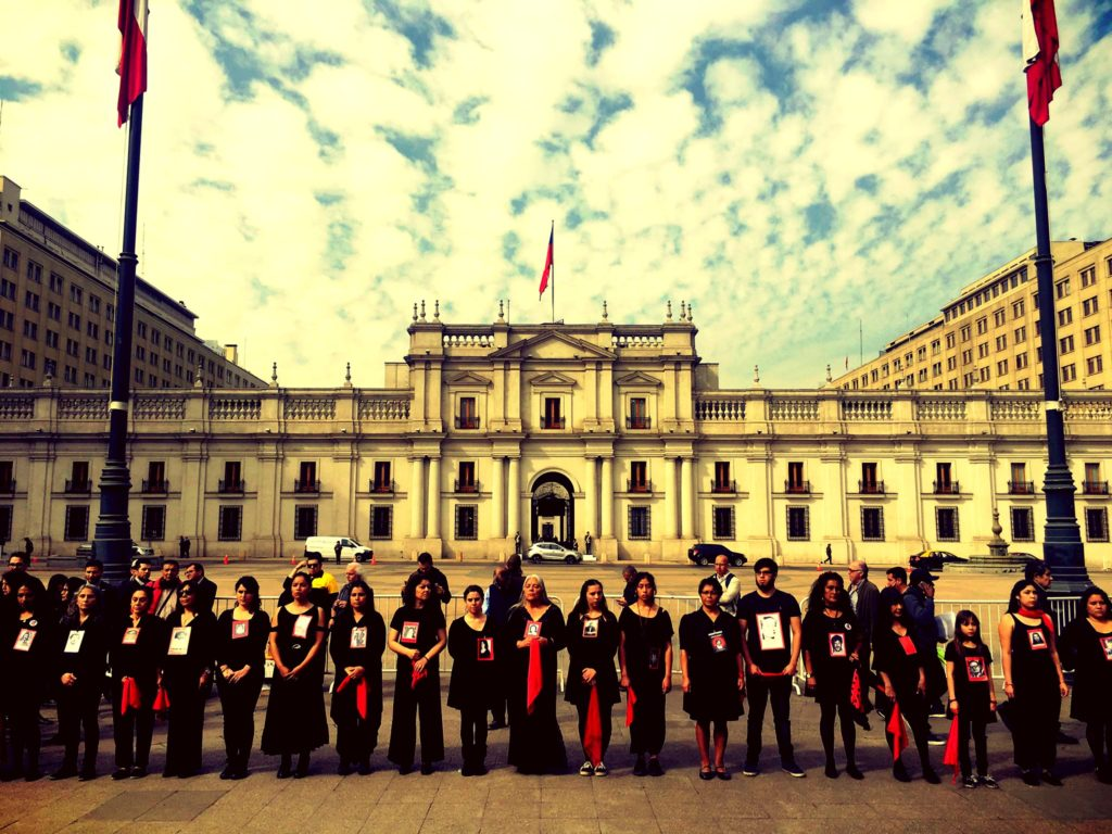 "Groups of individuals dressed in black standing in line with government building in background. Pictured is the ""Cueca Sola"" Collective outside of the Casa Moneda, the national palace in Santiago, Chile, which performs the Chilean national dance, known as ""cueca,"" which is always done with a partner. In remembrance the performances is done alone, ""sola,"" for one or more of the disappeared, often a friend or family member. Taken September 11, 2018."