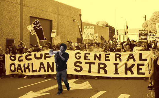 "Photo of Boots Riley with bull horn in front of banner saying ""occupy oakland, general strike"""