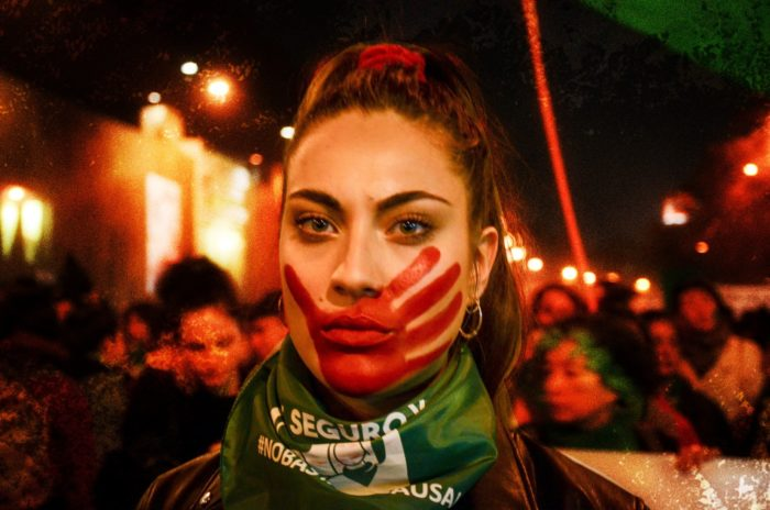 Image of woman at protest during evening. A hand painted in red is on her face, symbolic of deaths resulting from illegal abortion.