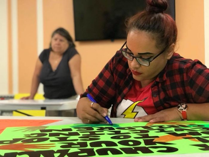 Woman making a protest placard with marker