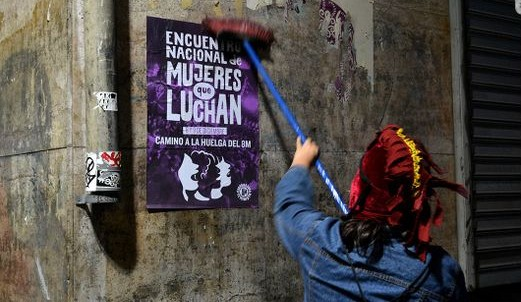 Woman facing away from camera holding brush as they affix a poster to a wall.
