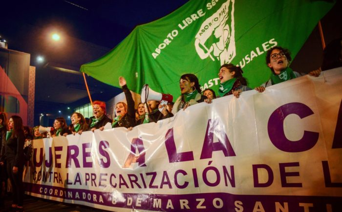 Women holding a banner leading a abortion rights protest in Chile.