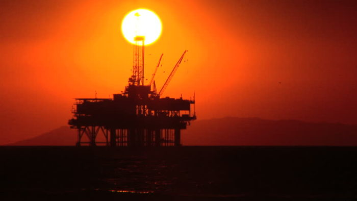 Ocean oil rig backed by a setting sun with a deep red sky.