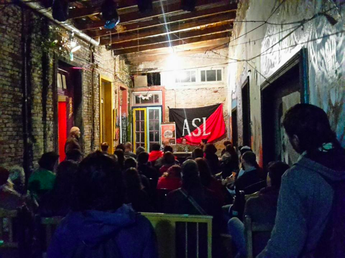 "Seated crowd facing towards a presentation, wall has large red and black flag with ""ASL."""