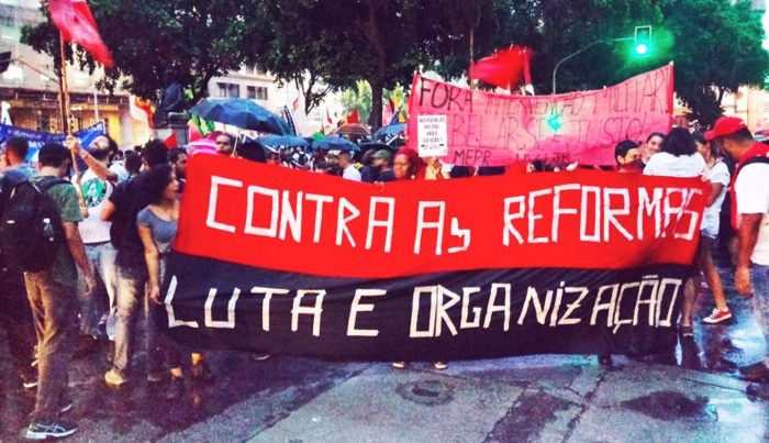 "Red and black banner being held during a demonstration reads in Portuguese ""Against the reforms / Struggle and organize"""
