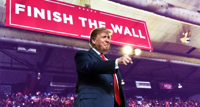 "Trump on stage at a campaign rally pointing towards audience, large banner in background ""finish the wall."""