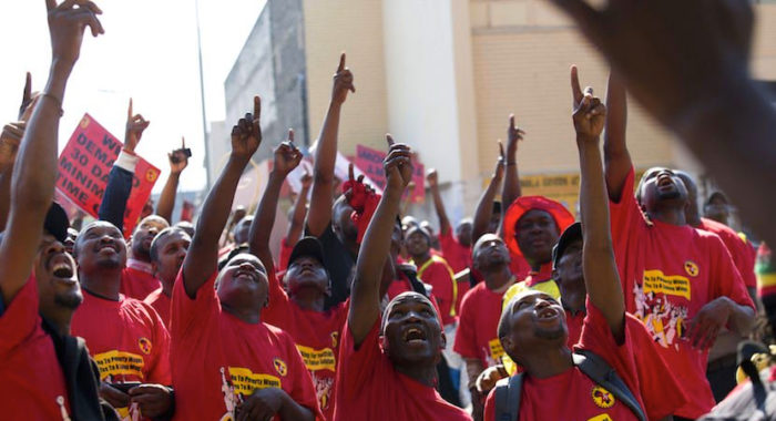 Rally of NUMSA union members, wearing red shirts pointing upwards.
