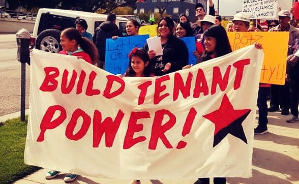 "Photo of tenants in LA Chinatown protesting displacement and holding banner with ""build tenant power!"" with red and black star."