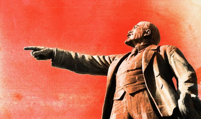Statue of Lenin pointing with red backdrop.