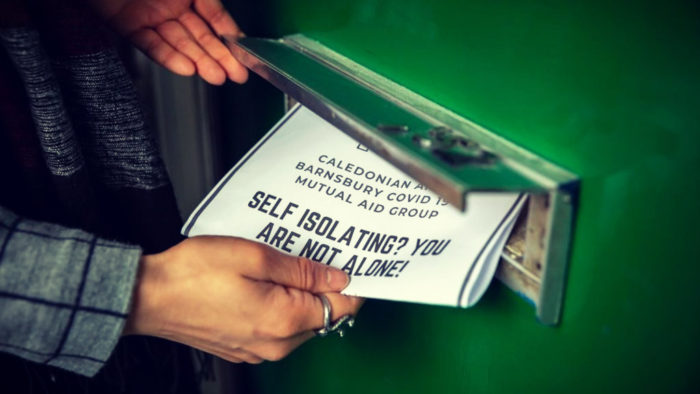 Image of someone inserting a flyer distributed by a mutual aid group in a door mail slot.