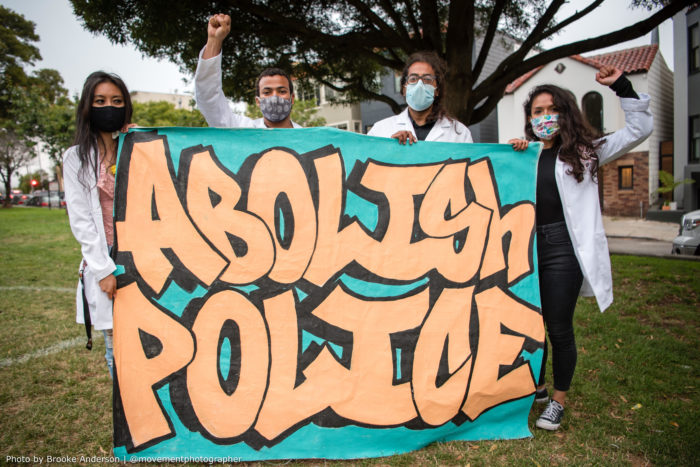 "Healthcare workers wearing lab coats holding banner with ""abolish police"""