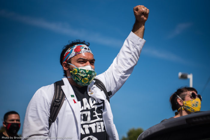 Man in white medical coast with raised fist in the air.