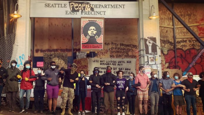 Line of CHOP supporters with linked arms in front of the boarded up Seattle police department building within the zone.